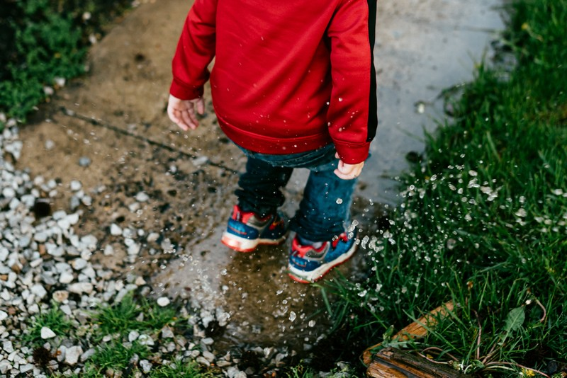 A boy splashes in a puddle