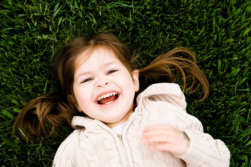 Preschool girl laughing in the grass